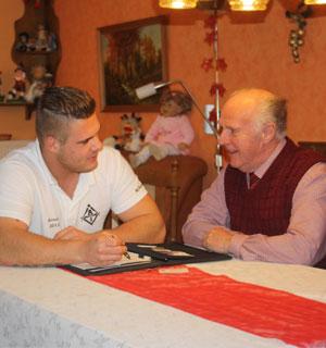 Inhaber Maximilian Petter führt ein Beratungsgespräch mit einem älteren Kunden