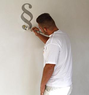 Impressum Stuckgeschäft Pulheim; Stuckateur Maximilian Petter malt mit einem Pinsel Paragraphen an die Wand
